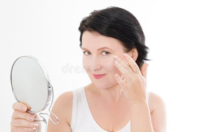 秀丽有镜子的中年妇女 面孔画象 在白色背景和防皱概念隔绝的温泉 成熟在整容手术白人妇女 免版税库存照片