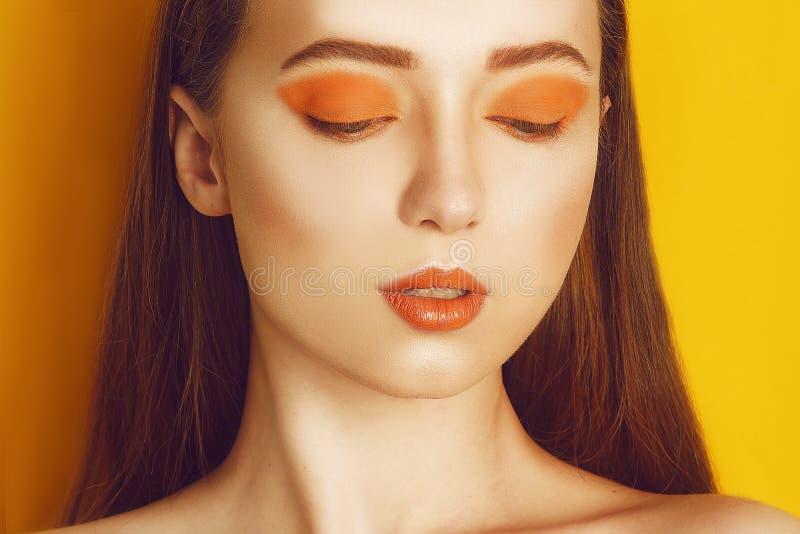 秀丽有黄色/橙色专业构成的模型女孩 橙色眼影和唇膏时尚妇女有长,直发的 免版税库存照片