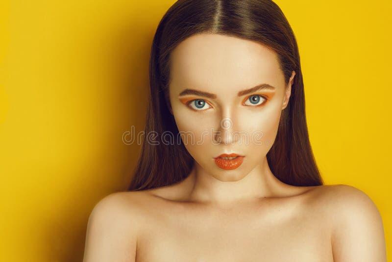 秀丽有黄色/橙色专业构成的模型女孩 橙色眼影和唇膏时尚妇女有长,直发的 库存图片