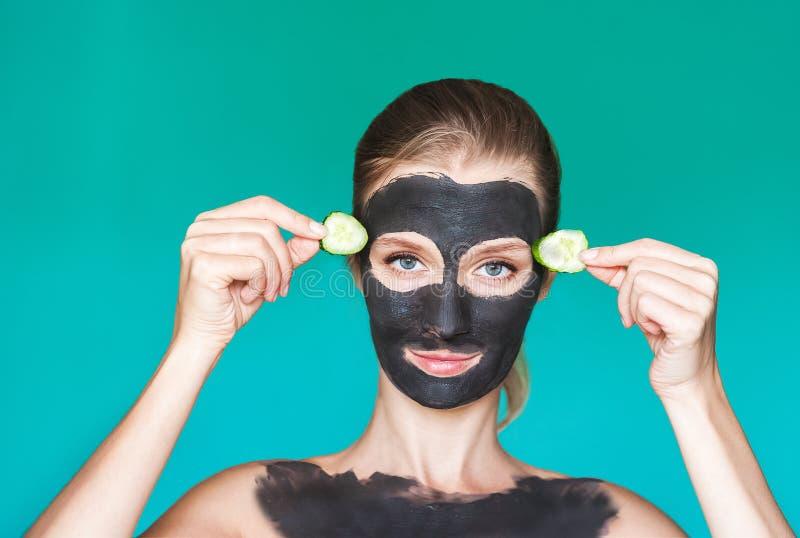 秀丽治疗 一个少妇在她的手上应用一个黑面具,在她的面孔与手接近,举行黄瓜的奶油 图库摄影