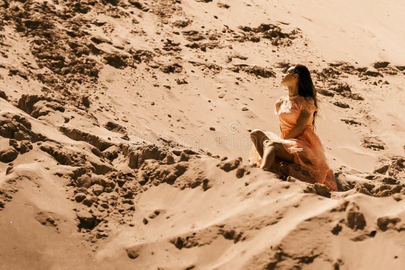 秀丽深色的女孩坐沙子在沙漠 免版税库存照片