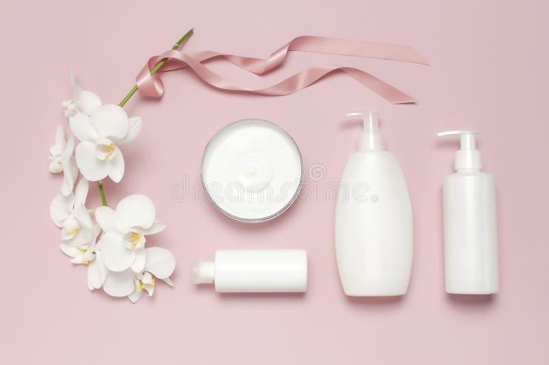 秀丽温泉概念 有奶油的,化妆瓶容器,在桃红色背景的白色兰花植物兰花花打开容器 免版税库存图片