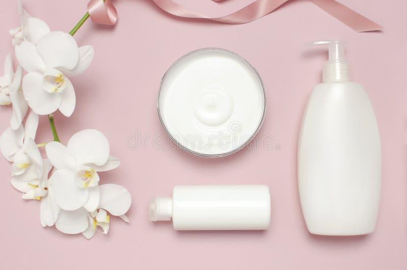 秀丽温泉概念 有奶油的,化妆瓶容器,在桃红色背景的白色兰花植物兰花花打开容器 库存照片