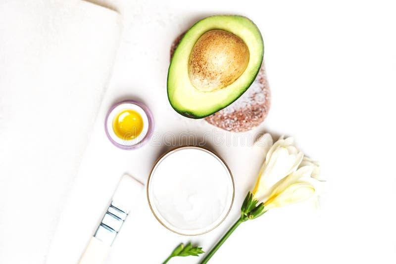 秀丽温泉蒸汽浴概念鲕梨、皮肤护理面部精华油、刷子、花和毛巾在白色背景, 免版税库存照片