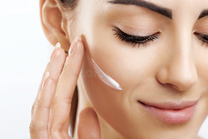 秀丽特写镜头愉快的年轻女人应用奶油于她的面孔Skincare和化妆用品概念 r r ?? 免版税库存照片