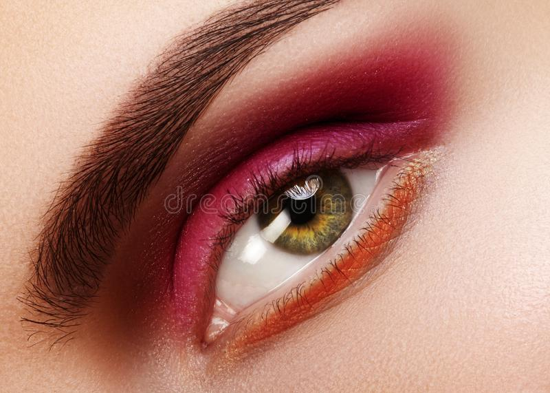 秀丽特写镜头美丽的女性眼睛 庆祝与红色眼影膏的时尚构成 圣诞节或情人节构成 库存照片