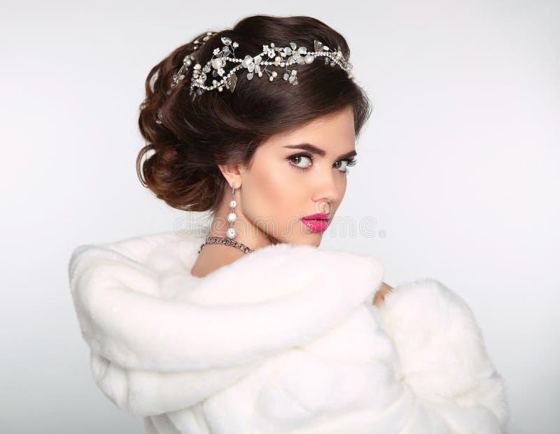 秀丽白色貂皮皮大衣的时装模特儿女孩 婚礼hairst 免版税库存照片