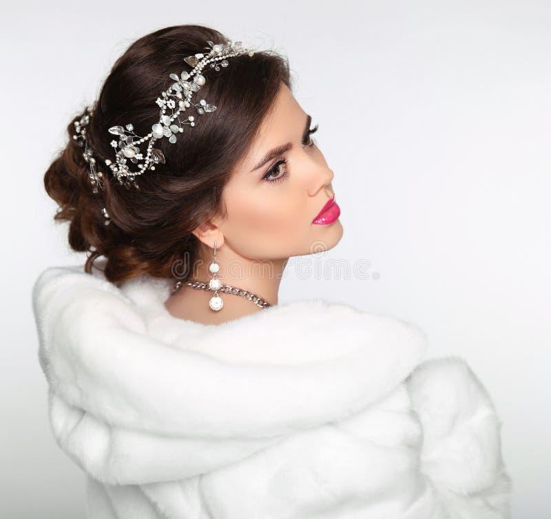 秀丽白色貂皮皮大衣的时装模特儿女孩 婚礼hairst 免版税库存图片