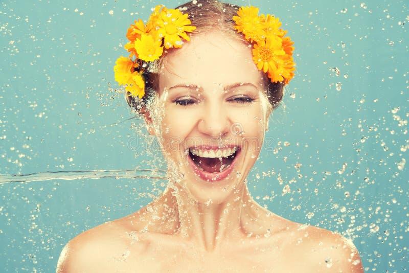 秀丽笑的女孩与飞溅水和黄色花 图库摄影