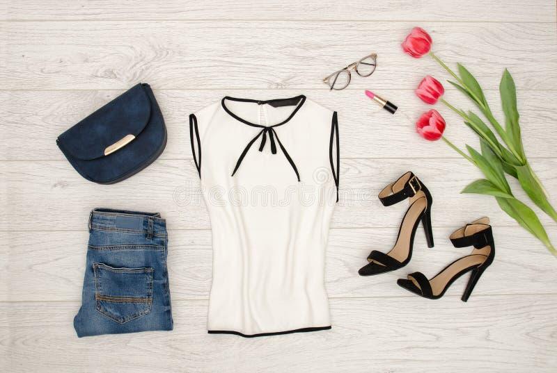 秀丽蓝色聪慧的概念表面方式构成妇女 白色女衬衫、蓝色提包、玻璃、唇膏、黑鞋子和桃红色郁金香 顶视图,轻的木背景 图库摄影