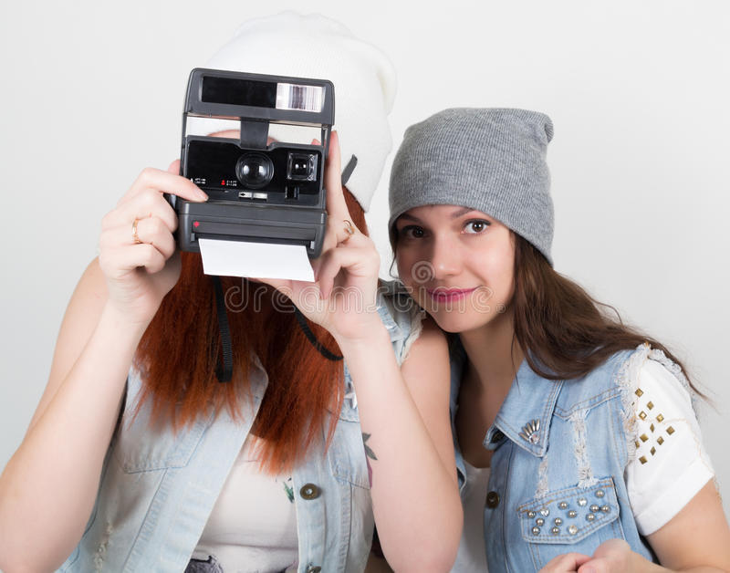 秀丽行家女孩黑和红色在太阳镜,做照片在照相机快照 少年鬼脸 免版税库存照片