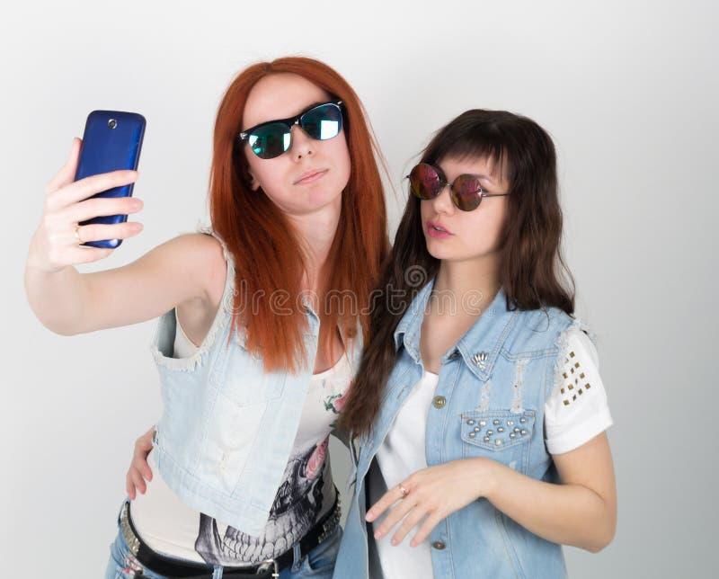 秀丽行家女孩黑和红色在太阳镜,做selfie在电话 少年鬼脸 免版税库存照片