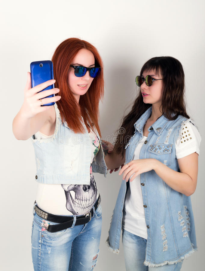 秀丽行家女孩黑和红色在太阳镜,做selfie在电话 少年鬼脸 库存照片