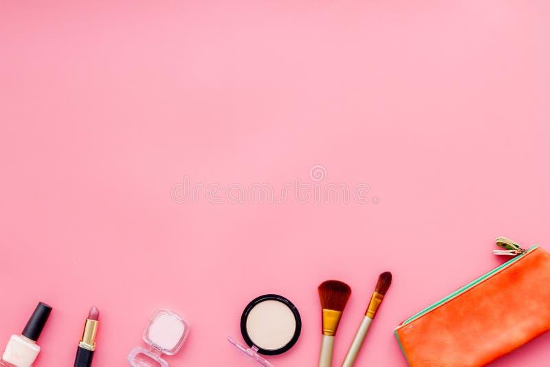 秀丽设置与装饰化妆用品 指甲油、刷子和袋子在桃红色背景顶视图大模型 免版税库存图片