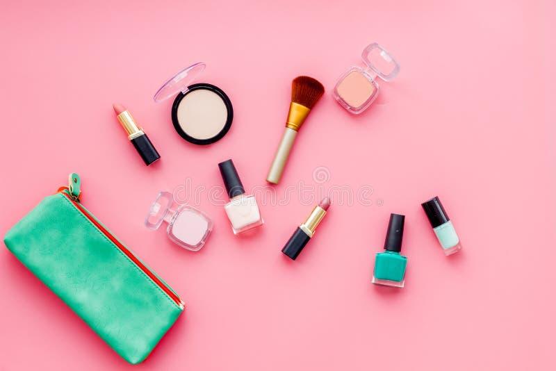 秀丽设置与装饰化妆用品 指甲油、刷子和袋子在桃红色背景顶视图大模型 免版税库存照片