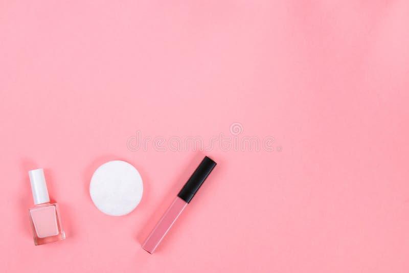 秀丽设置与装饰化妆用品 指甲油、刷子和袋子在桃红色背景顶视图大模型 库存图片