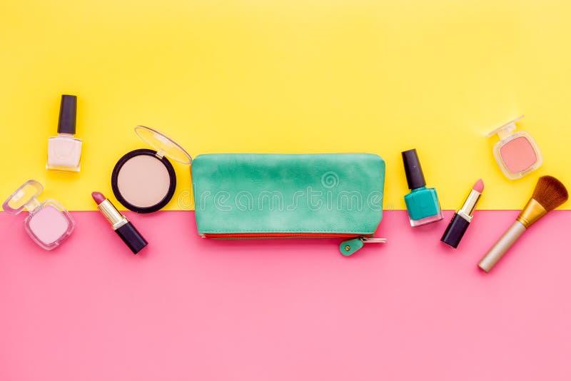 秀丽设置与装饰化妆用品 指甲油、刷子和袋子在黄色和桃红色背景顶视图大模型 图库摄影