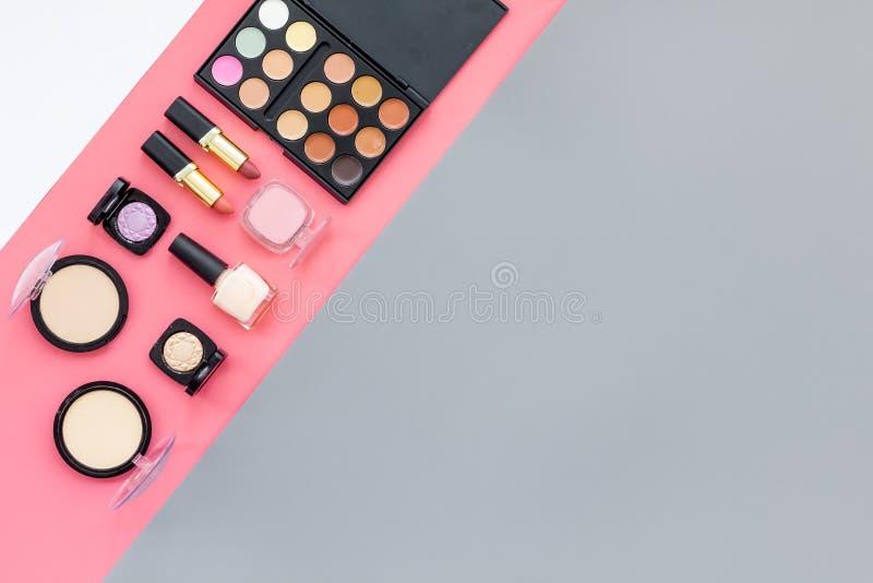 秀丽设置与装饰化妆用品 眼影膏调色板,在桃红色和灰色背景顶视图大模型的刷子 免版税图库摄影