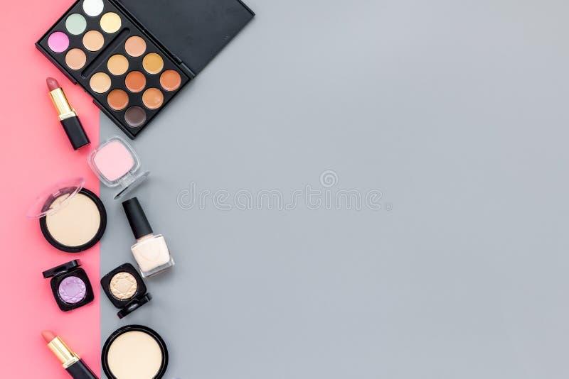 秀丽设置与装饰化妆用品 眼影膏调色板,在桃红色和灰色背景顶视图大模型的刷子 图库摄影