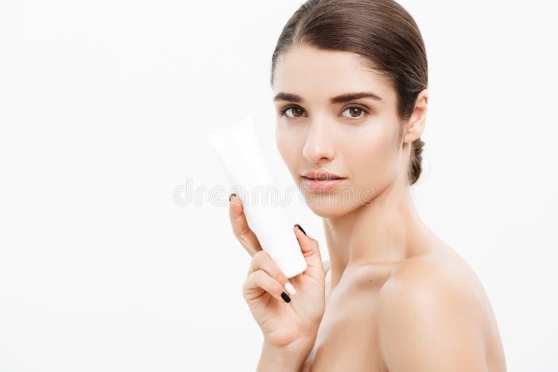秀丽青年护肤概念-拿着和提出奶油色管产品的美丽的白种人妇女面孔画象 免版税库存照片