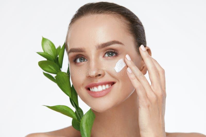 秀丽面孔关心 有奶油的妇女在面部皮肤 免版税库存图片