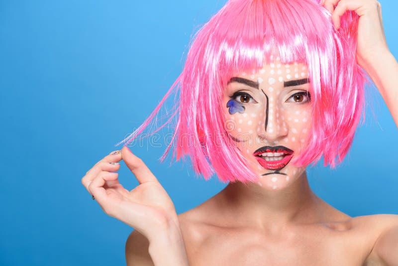 秀丽顶头射击 有创造性的流行艺术的少妇组成并且变粉红色看在蓝色背景的假发照相机 免版税库存图片