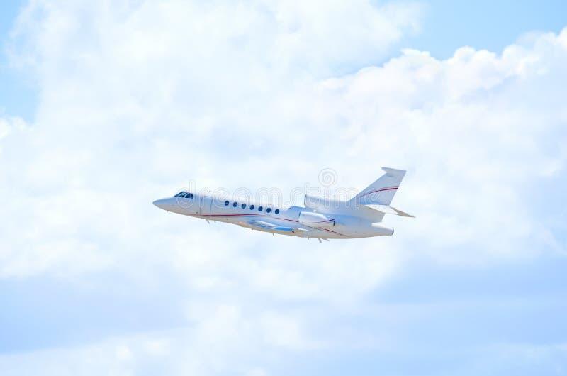 私人企业喷气机班机飞机在飞行中反对蓬松云彩 库存照片
