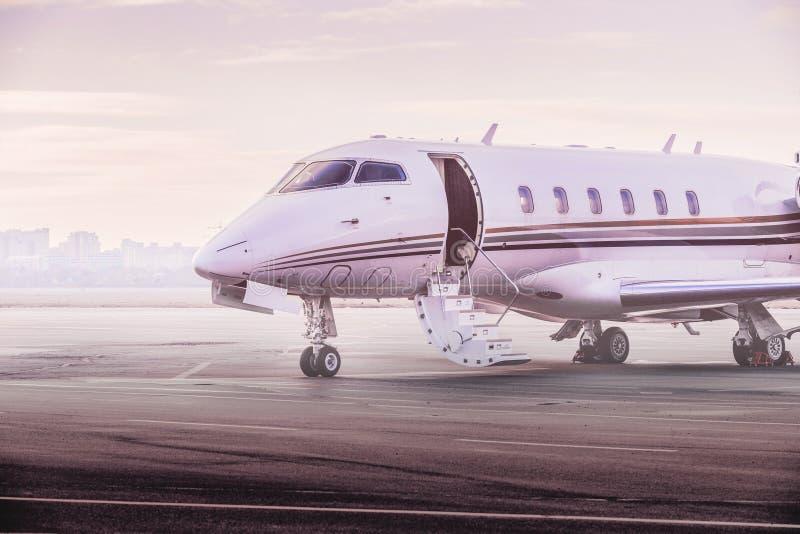 私人喷气式飞机飞机停车处在机场 在日落的私有飞机, 免版税库存照片