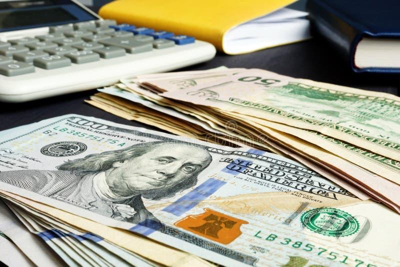 私人预算或财富 美元和计算器在桌上 免版税库存图片