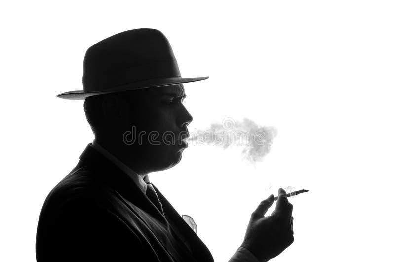私家侦探剪影点燃香烟 代理看起来艾尔・卡彭停留旁边对照相机 在黑色a的警察犯罪场面 库存图片