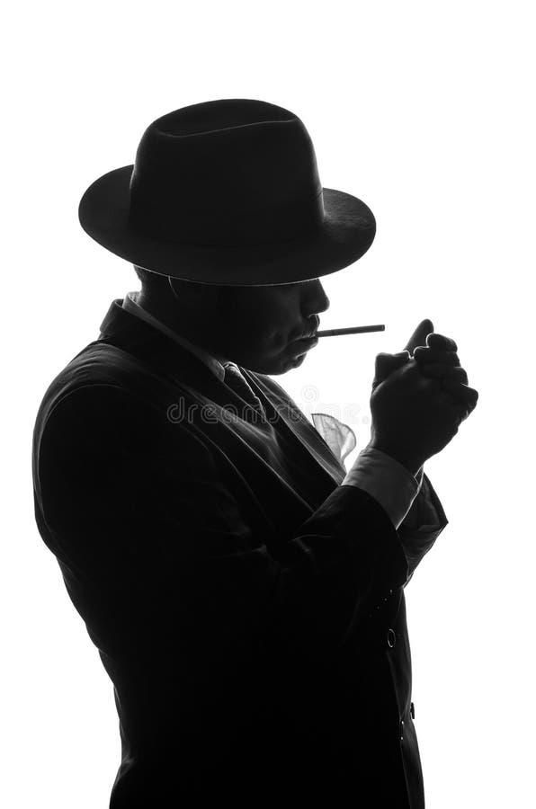 私家侦探剪影点燃香烟 代理看起来艾尔・卡彭停留旁边对照相机 在黑色a的警察犯罪场面 库存照片