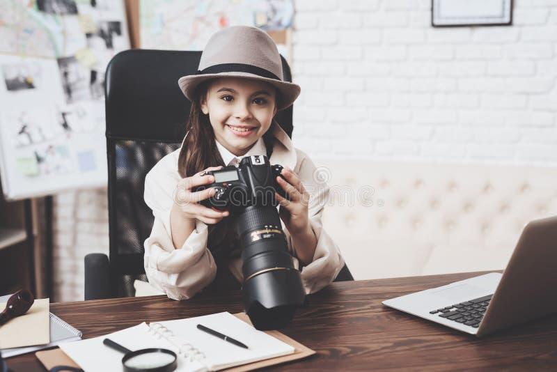 私家侦探机构 小女孩坐在看照片秘密审议的书桌 库存照片