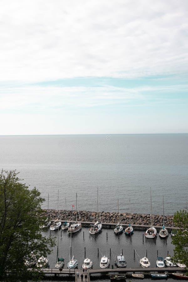 私有小船的小跳船 私有小船和小船在码头在海反对天空蔚蓝 钓鱼在的汽船 免版税图库摄影