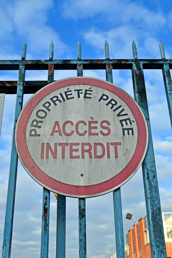 私有财产,作为文本的禁止的通入在葡萄酒铁锈的影响的金属篱芭的法语,禁区, 免版税库存照片