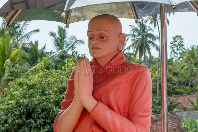 秃头修士雕象在佛教寺庙的伞下 免版税图库摄影