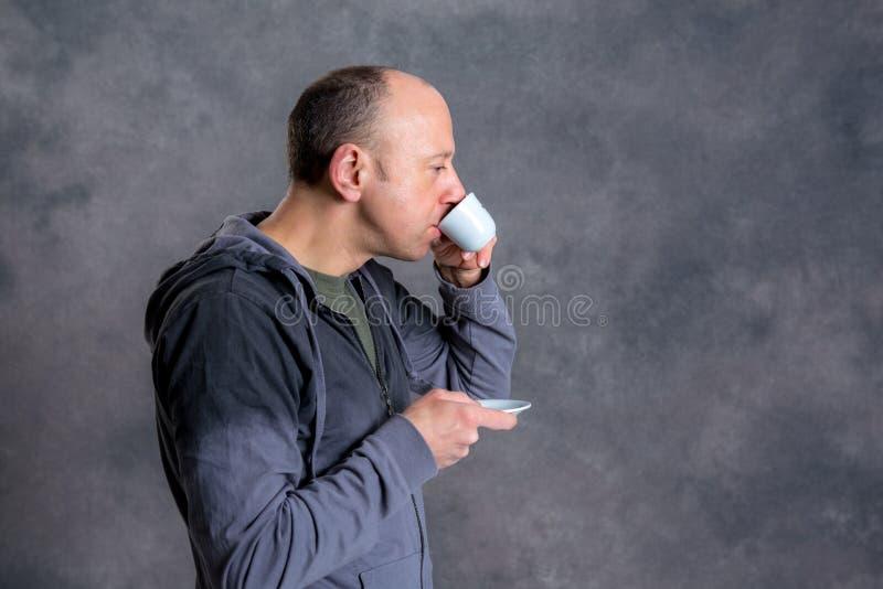 年轻秃顶的人饮用的咖啡 免版税库存图片