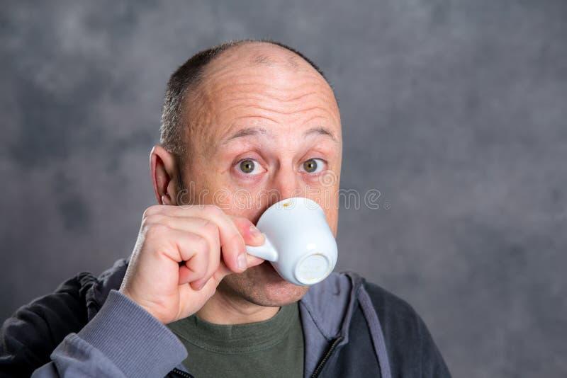 年轻秃顶的人饮用的咖啡 库存图片