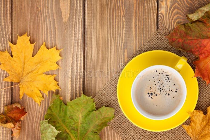 秋叶和咖啡杯在木背景 免版税库存图片