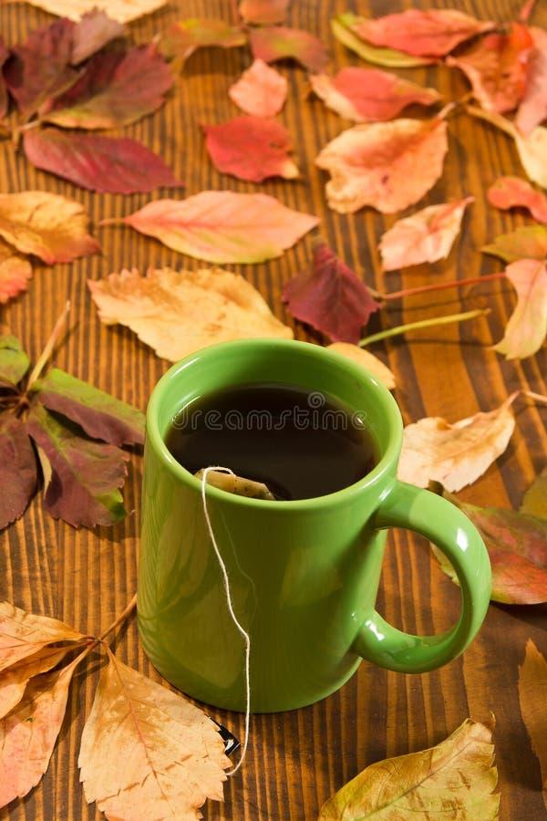 秋叶和茶杯在木背景 免版税图库摄影