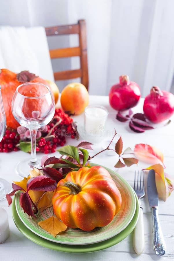 秋天万圣夜或感恩天桌设置 下落的叶子、南瓜、香料、空的板材和利器在木 免版税库存图片