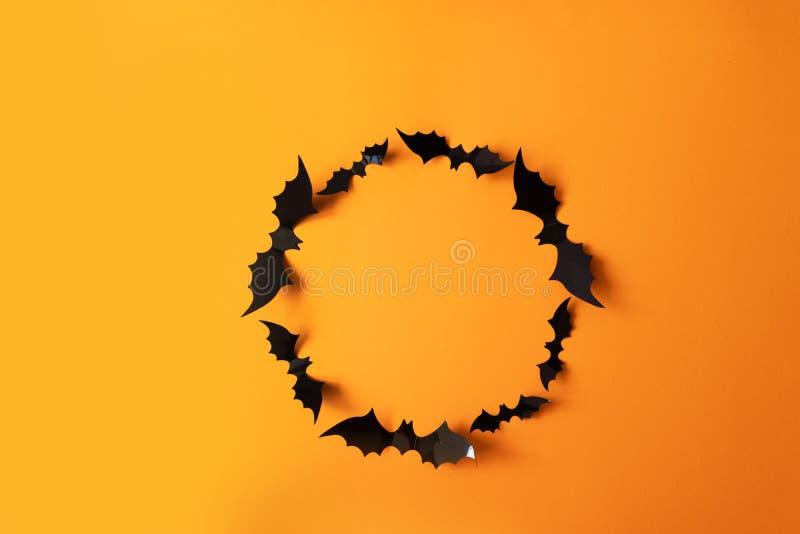 秋天万圣节结构的黑纸棒飞行在橙色背景 库存图片