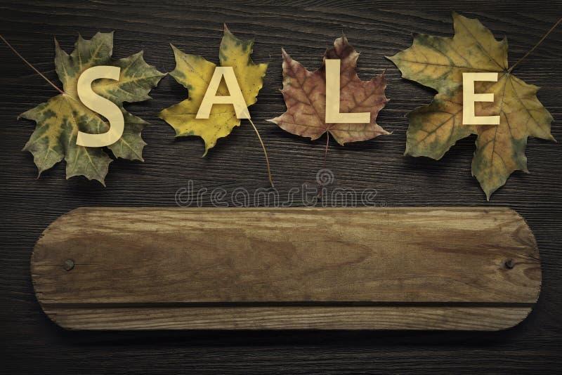 秋天与木标志的广告销售词的和题字和b 免版税库存照片