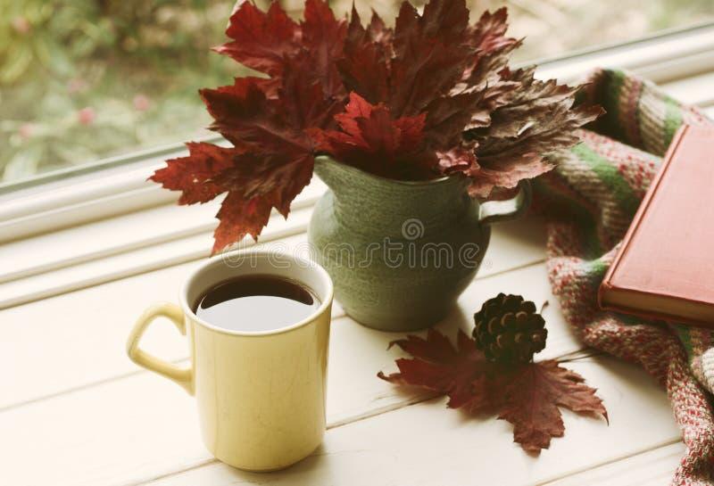 秋天与红槭叶子的静物画安排在一个花瓶、黄色咖啡杯和一本书在白板表上在风前面 库存照片