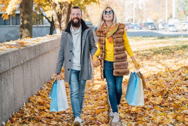 秋天乐趣夫妇购物边路离开秋天 免版税图库摄影