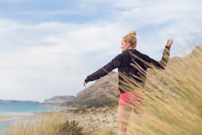 去年秋天享受太阳的自由的愉快的妇女在度假 免版税库存照片