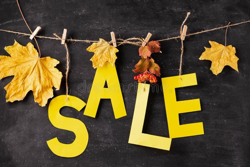 秋天从黄色纸和干燥叶子的折扣信件在黑粉笔板 秋天销售概念 季节性提议 免版税库存图片