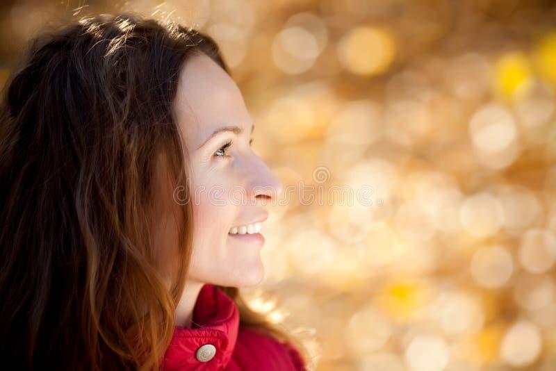 秋天公园微笑的妇女 免版税图库摄影