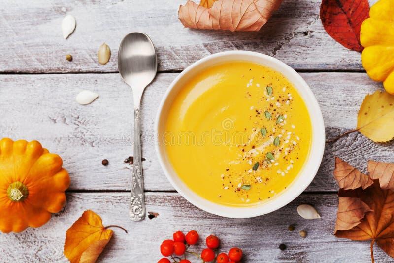 秋天南瓜汤装饰了种子和麝香草在白色碗在土气木台式视图 在万圣夜射击的舒适生活方式 库存图片