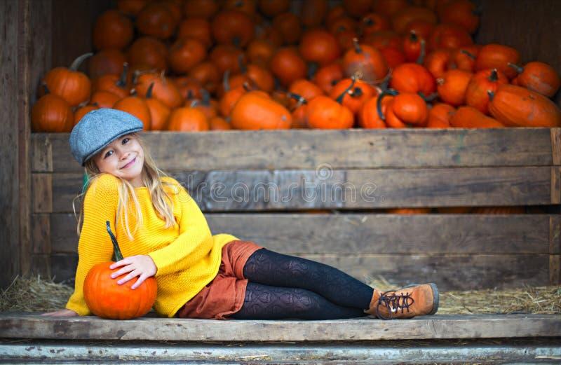 秋天南瓜补丁背景的愉快的女孩 库存照片