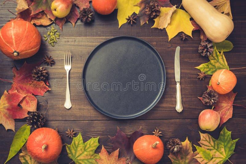 秋天和感恩天与下落的叶子、南瓜、香料、空的黑盛肉盘和葡萄酒利器的桌设置在棕色w 免版税库存照片